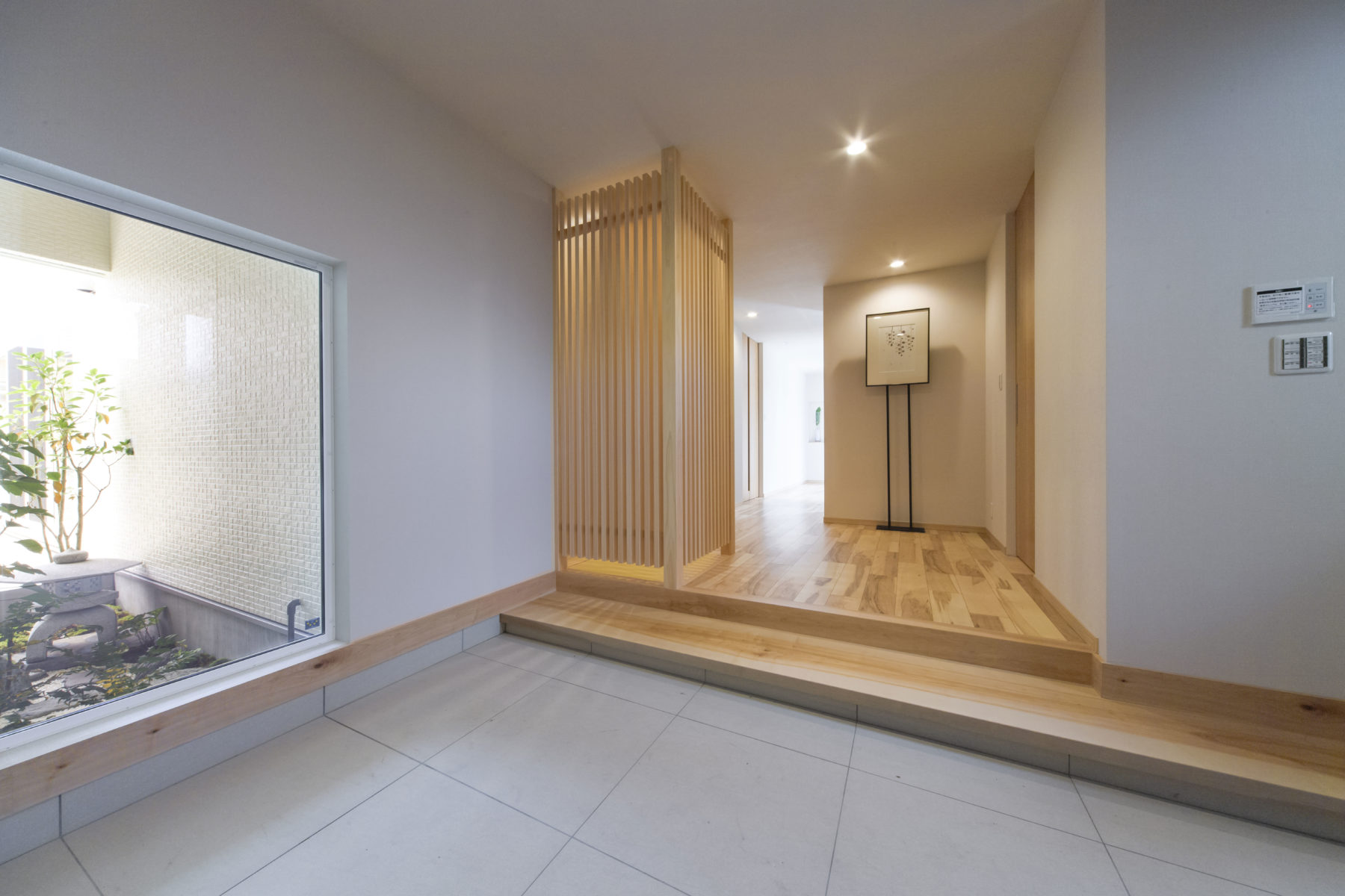 玄関ではヒノキの格子と坪庭が、和のくつろぎを演出します。