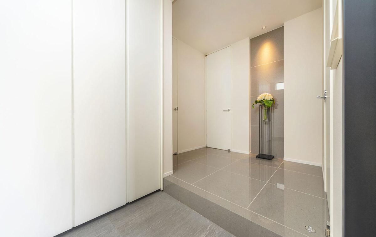 グレー色の床タイルと白い壁とのコントラストは、シンプルながら高級感を併せ持ち ちょっとしたスタンドフラワーが季節の美しさを感じさせてくれます。