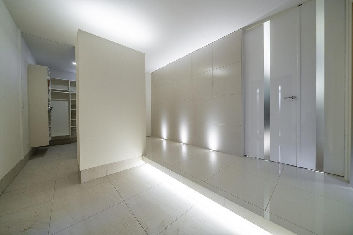 床・壁・天井を効果的に照らす間接照明の光が高級感のあるホテルのようなエントランスを演出しています。また、リビングへの入り口には鏡面のハイドアを採用し、空間に広がりを与えてくれます。