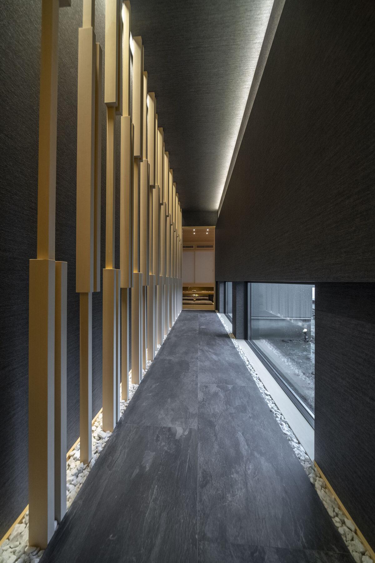 エントランスから和室へと誘う回廊は、黒い石畳と格子による和の空間、間接照明による光の陰影の演出で来訪者を楽しませてくれます。