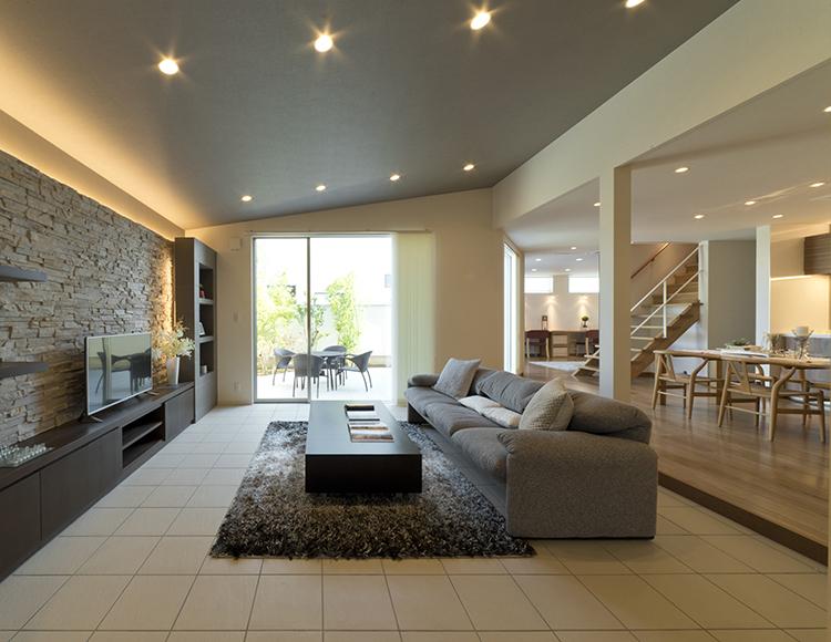 実は、天井が斜めに設計されています。勾配天井も、空間を広く感じさせるポイントです。 壁一面にタイルを施したテレビステーションは、間接照明による陰影が美しく空間を引き立ててくれ、その場にいるだけで気分を明るくさせてくれます。