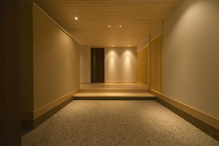 玄関に一歩入ると、洗い出しの落ち着いた空間が訪れた人を迎え入れます。広々とした玄関ホールと、壁に落としたダウンライトが、さらにゆったりとした和の風情を演出します。 右横の扉をあけると家族専用の玄関があり、靴やコート、庭道具などが収納でき、ホールに直接上がれるようになっています。