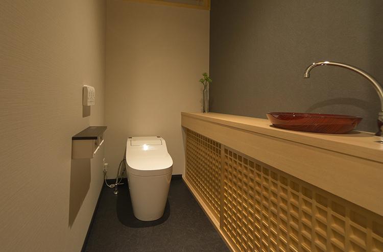 トイレにも和の設えは忘れません。造作の手洗い収納を格子戸にすることで風情あるトイレを演出しています。 朱色の手洗いガラスボウルが、空間に繊細さと華やかさをプラスしています。