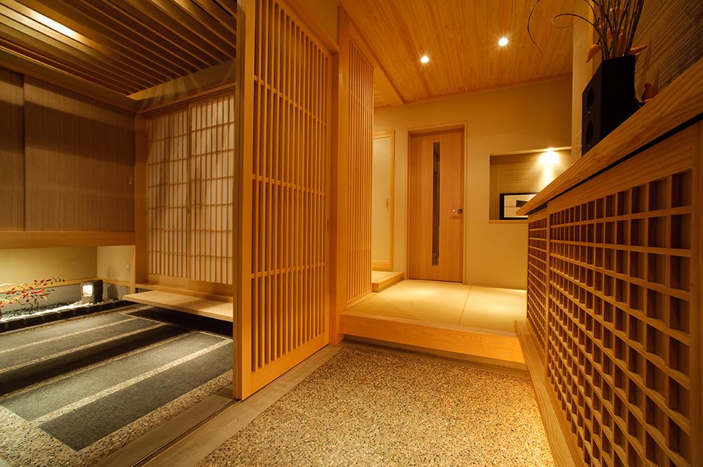 玄関に一歩入った瞬間から、美しい和の装いが出迎えます。 洗い出しの玄関と畳張りの玄関ホール、檜の板張りの天井は、まるで旅館に訪れたかのような寛ぎの空間を演出します。 左の格子戸を開けると和室へと続く石畳があり、お客様をゆったりとおもてなししてくれます。
