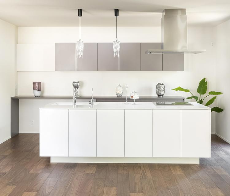 お料理がしやすいアイランドキッチンも、クオレオリジナルの輸入造作です。 白の鏡面素材が美しいキッチンは、リビング側にも収納がついており、見た目と機能性を兼ね備えています。