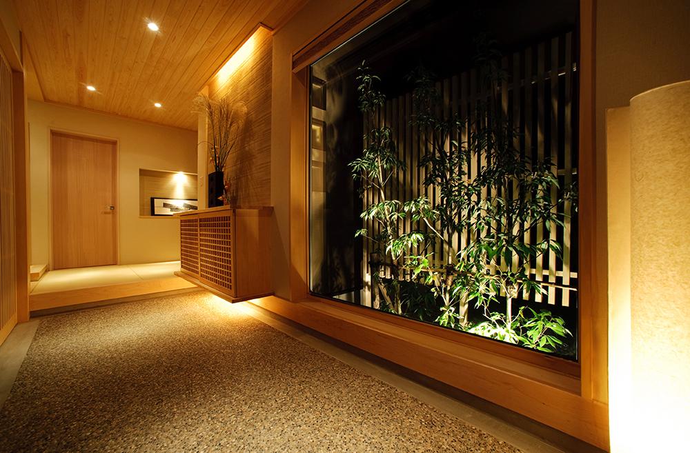 玄関の右手には坪庭を臨む大きな窓があります。 訪れるお客様にもお日本の四季折々の美しさを楽しんでいただくことができます。また、開放な窓の奥行によって玄関が広く見えます。