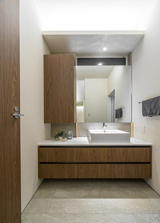 清潔感のある洗面台も、標準装備のオリジナル造作家具です。 大容量の収納で、すっきり感を保てる工夫がされています。 左右にはランドリールームとお風呂場が繋がっており、家事動線もスムーズです。