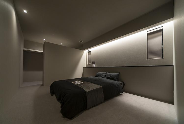 1日の疲れをとる寝室は、落ち着いたカラーコーディネートで、ホテルライクに仕上げました。間接照明の優しい光がグレーの壁に映え、癒しの空間を作っています。 カーペット敷きの空間は、温かみと高級感を感じさせます。